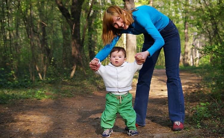 В этом возрасте малышу уже может гулять не только в коляске, но и своими ножками, держась за руки родителей.