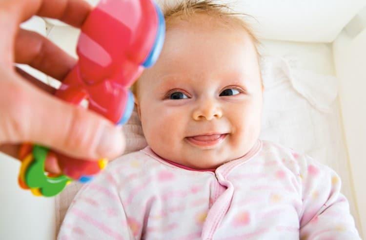 Малыш уже может сосредоточить взгляд на яркой игрушке.