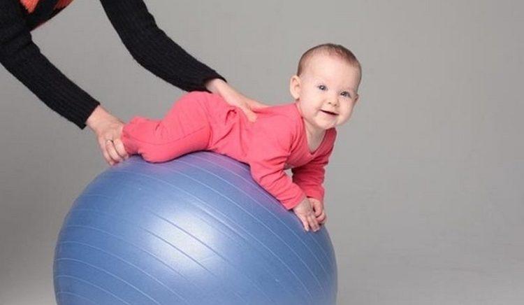 такое упражнение на фитболе поможет укрепить позвоночник и пресс ребенка.