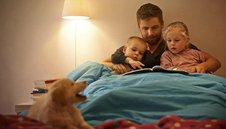 Один из способов, как научить ребенка засыпать без укачивания, это определенные традиции, например, чтение книги перед сном.